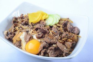 gyūdon qui consiste en un bol de riz chaud surmonté de lamelles de bœuf, d'oignon et parfois d'oeu